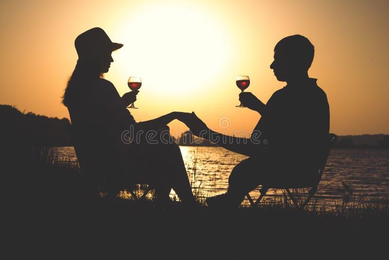 Profilo di giovani coppie che si rilassano sulla banca del fiume all'alba con un bicchiere di vino sulle sedie immagini stock libere da diritti