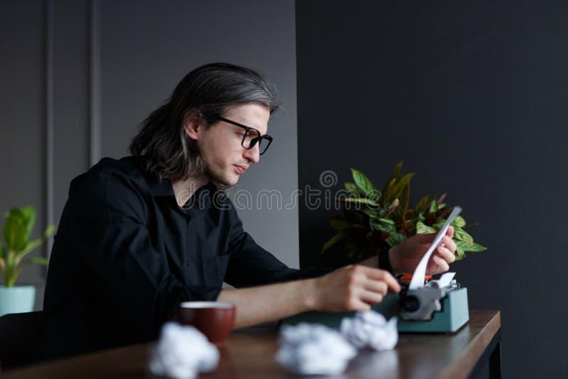 Profilo di un giovane in abbigliamento d'annata che inserisce nuova carta nella macchina da scrivere, sopra fondo giallo Copi lo  fotografie stock