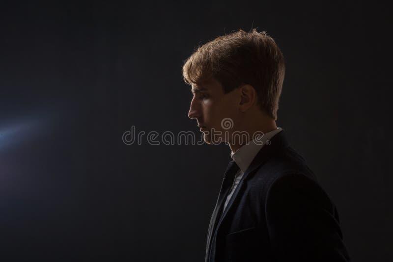 Profilo di un giovane in un vestito su un fondo nero fotografia stock libera da diritti