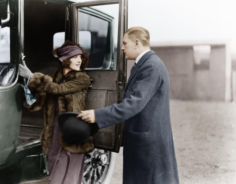 Profilo di un uomo che aiuta una giovane donna a imbarcarsi su un'automobile (tutte le persone rappresentate non sono vivente più immagine stock libera da diritti