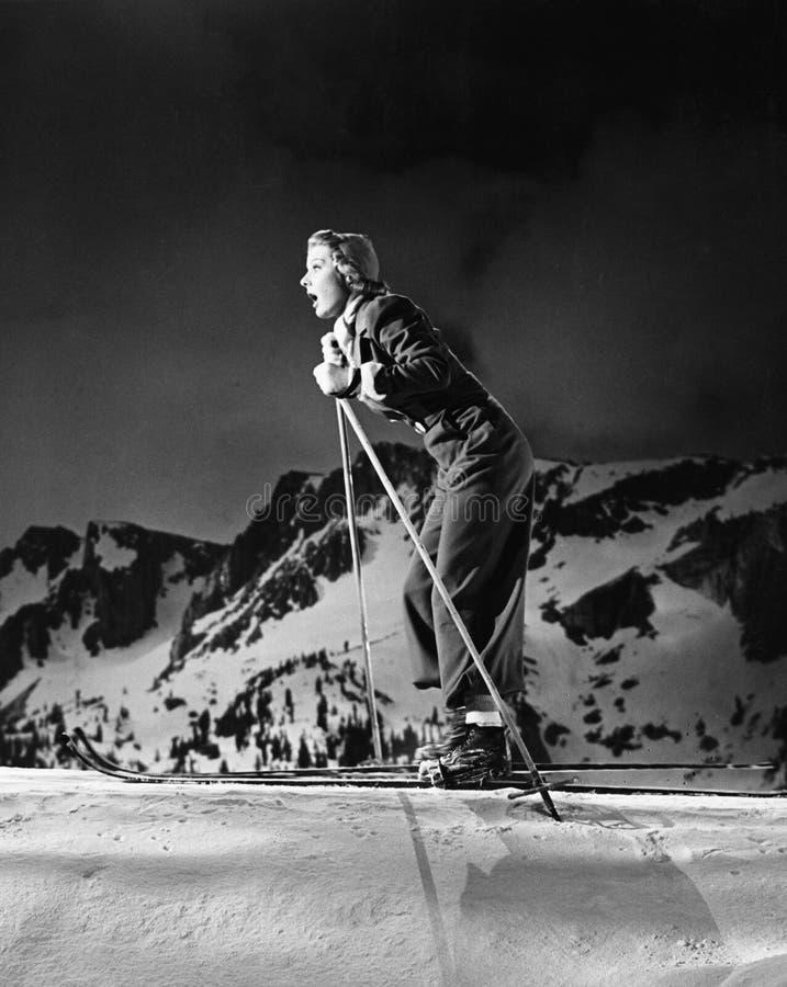 Profilo di una corsa con gli sci della giovane donna (tutte le persone rappresentate non sono vivente più lungo e nessuna proprie fotografia stock libera da diritti