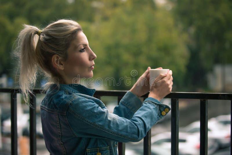 Profilo di una donna bionda che sta sul portico fotografia stock libera da diritti