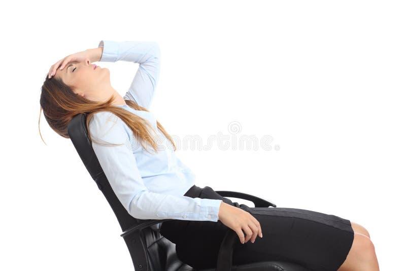 Profilo di una donna di affari stanca che si siede su una sedia fotografia stock