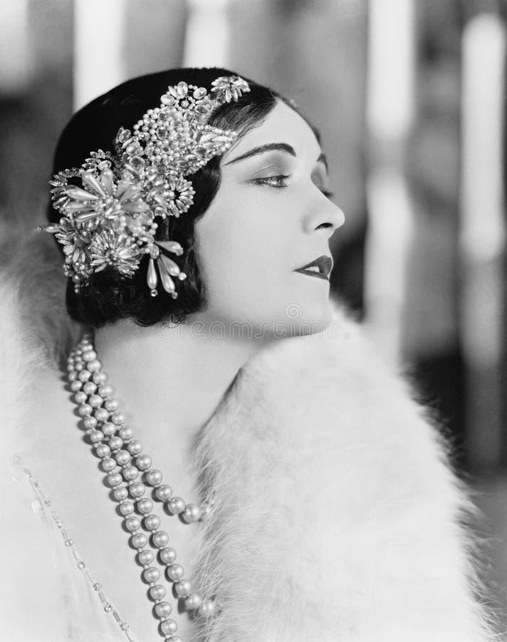 Profilo di una donna elegante che indossa un pezzo ingioiellato dei capelli (tutte le persone rappresentate non sono vivente più  fotografia stock libera da diritti