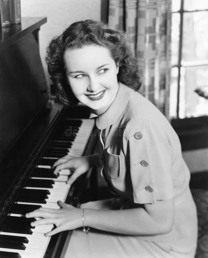 Profilo di una giovane donna che gioca un piano e sorridere (tutte le persone rappresentate non sono vivente più lungo e nessuna  immagini stock libere da diritti