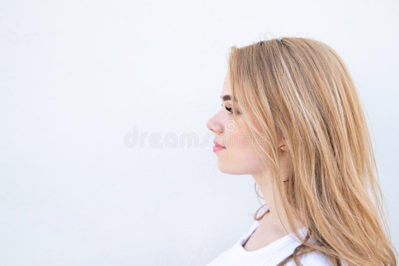 Profilo di una ragazza bionda della ragazza adorabile sui precedenti di una parete bianca fotografie stock