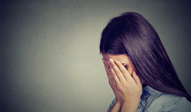 Profilo laterale di una donna triste che copre il suo fronte di mani fotografia stock