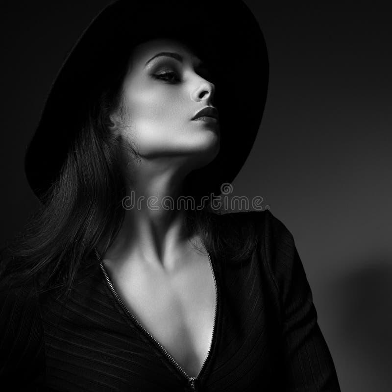 Profilo sexy della donna di trucco di fascino che posa in cappello di modo su buio fotografia stock libera da diritti
