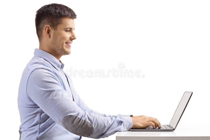 Profilo sparato di un giovane che scrive su un computer portatile immagini stock libere da diritti