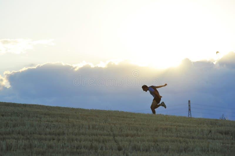 Profilowa sylwetka młodego człowieka bieg w wsi ćwiczy definitywnego sprint na zmierzchu obrazy royalty free