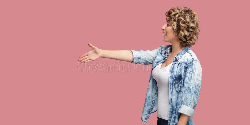Profilowy bocznego widoku portret patrzeje naprzód i daje ręce witać szczęśliwa młoda kędzierzawa kobieta w przypadkowej błękitne obrazy stock