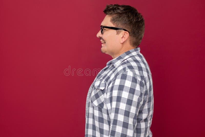 Profilowy bocznego widoku portret szczęśliwy przystojny w średnim wieku biznesowy mężczyzna stoi i patrzeje w przypadkowej w krat fotografia royalty free