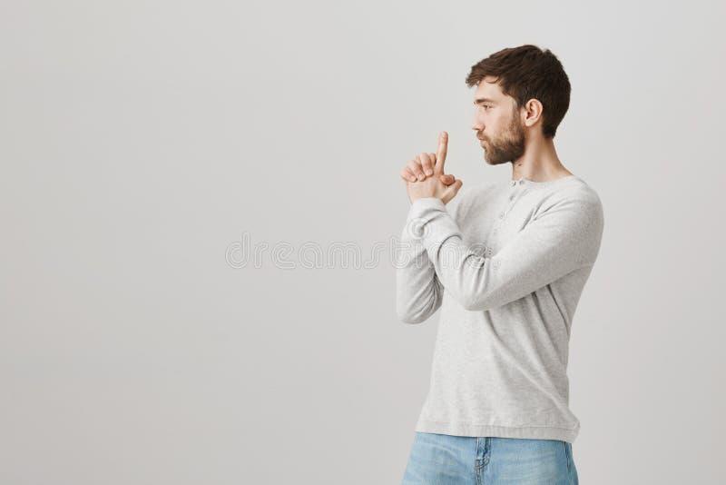 Profilowy portret figlarnie atrakcyjny caucasian facet z brodą, pokazuje armatniego gest i działanie tak jakby jest żołnierzem lu fotografia royalty free