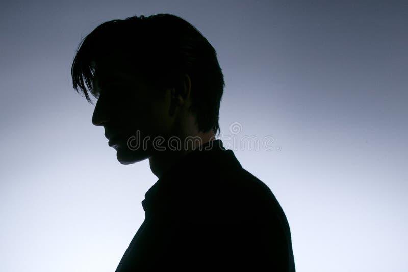 Profilowy portret m?ody cz?owiek w czarnym kostiumu, pozy w ciemno?ci, odizolowywaj?cej na bia?ym tle Horyzontalny indoors strzel zdjęcie royalty free