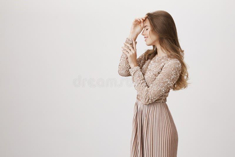Profilowy portret powabna elegancka caucasian kobieta delikatnie dotyka czoło gestykuluje i tak jakby przywoływać uroczy zdjęcie stock