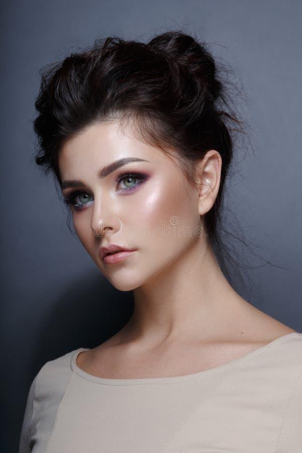 Profilowy portret zmys?owa m?oda kobieta, fryzura i doskonali? makija? na popielatym tle, Pionowo widok fotografia royalty free