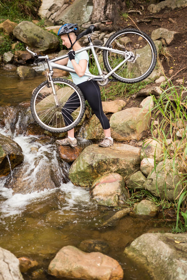 Profilowy widok dysponowana kobieta podnosi jej rower fotografia stock