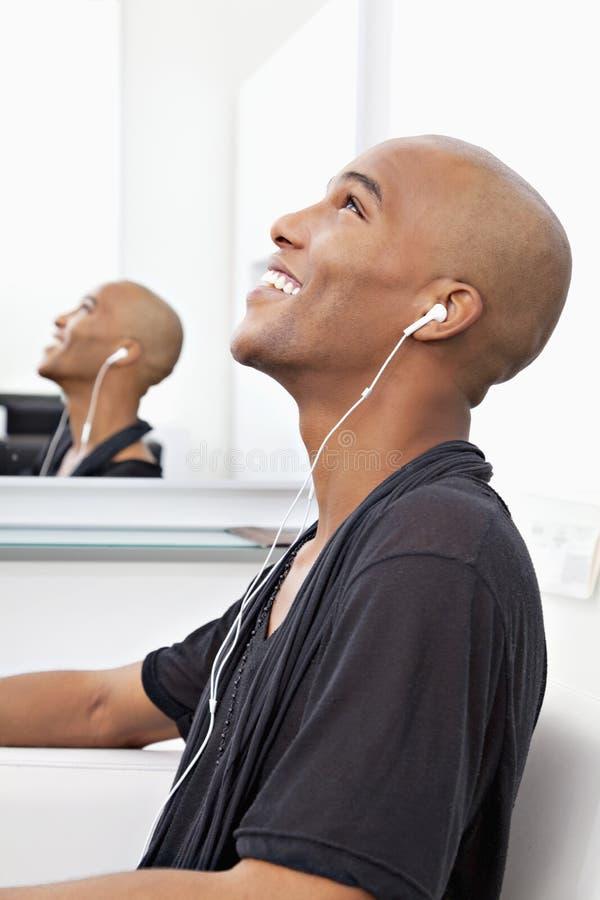 Profilowy widok mężczyzna słuchająca muzyka przy salonem zdjęcie stock