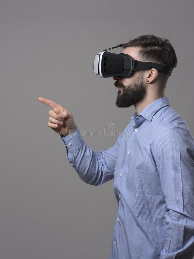 Profilowy widok młody biznesowy mężczyzna dotyka interaktywnego zwiększającego rzeczywistość dotyka ekran z palcem z vr słuchawki obrazy royalty free