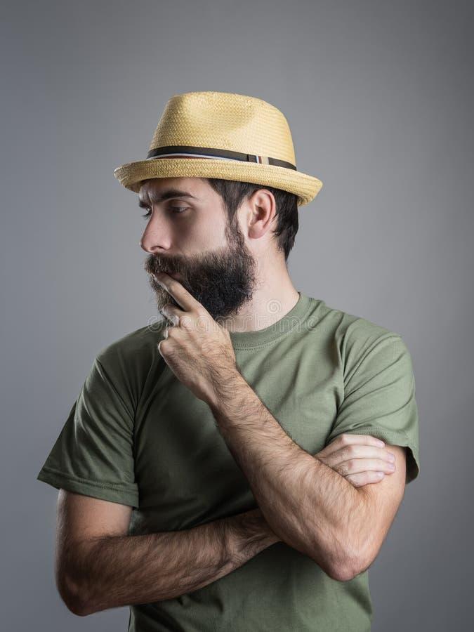 Profilowy widok młody zadumany brodaty mężczyzna jest ubranym słomianego kapelusz dotyka jego brodę zdjęcia stock
