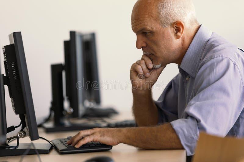Profilowy widok pracuje przy komputerem starszy mężczyzna obraz royalty free