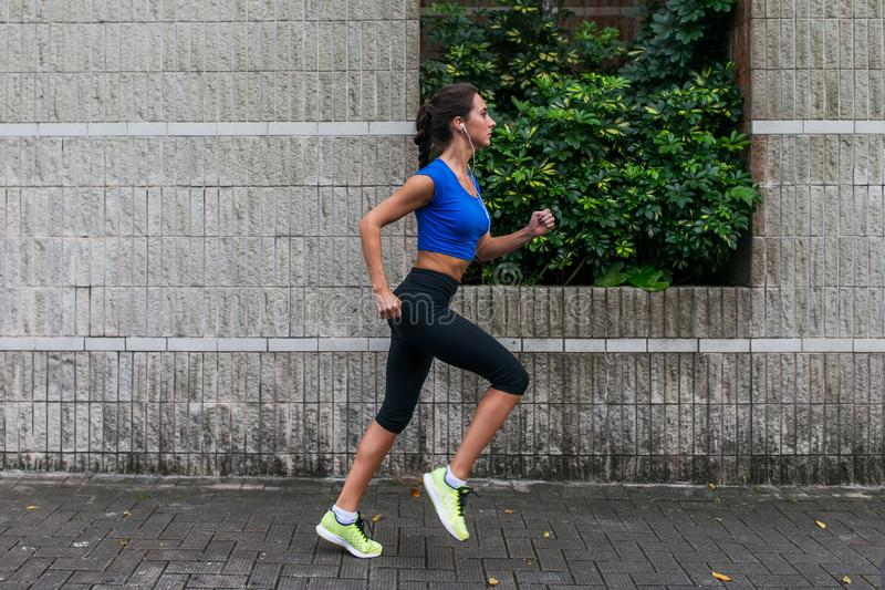 Profilowy widok sporty młoda kobieta pracująca out outdoors Sprawności fizycznej dziewczyny bieg na chodniczku obrazy royalty free