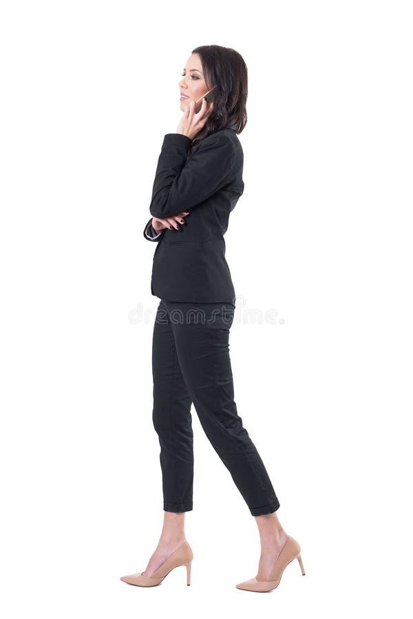 Profilowy widok szczęśliwa elegancka biznesowa kobieta w kostiumu odprowadzeniu i mieć rozmowie na telefonie komórkowym fotografia stock