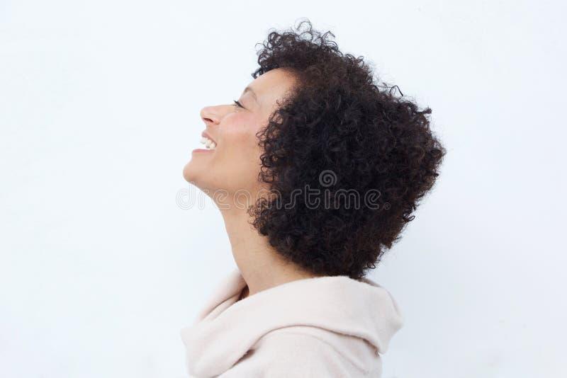 Profilporträt der Frau lachend gegen weißen Hintergrund lizenzfreies stockbild