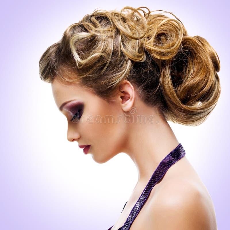 Profilporträt der Frau mit Modefrisur stockbild