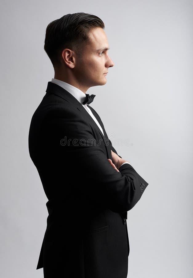 Profilporträt eines sexy Mannes im schwarzen Anzug Getrennt lizenzfreie stockfotografie