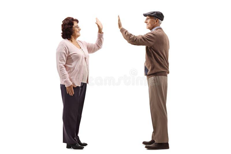 Profilschuß in voller Länge einer älteren Frau hoch--fiving ein älterer Mann lokalisiert auf weißem Hintergrund lizenzfreies stockbild