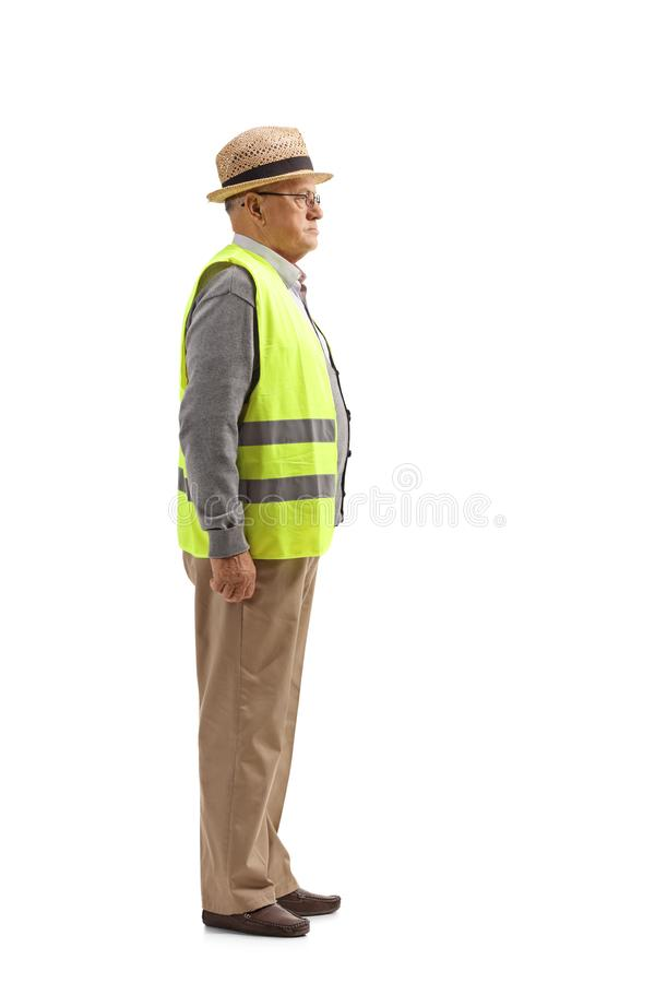 Profilschuß in voller Länge eines älteren Mannes mit einer Sicherheitswestenstellung lizenzfreie stockbilder