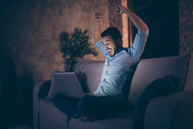 Profilseitenansicht seines netten, glücklich glücklich glücklichen Brunet-Typen, der mit Laptop auf Divan sitzt stockbild