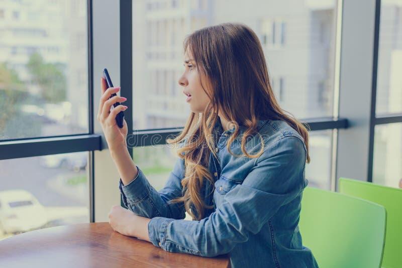 Profilsidan vände tätt upp siktsfotoståenden av den besvikna frustraited ledsna upprivna olyckliga damen som ser mobiltelefonen f royaltyfri fotografi