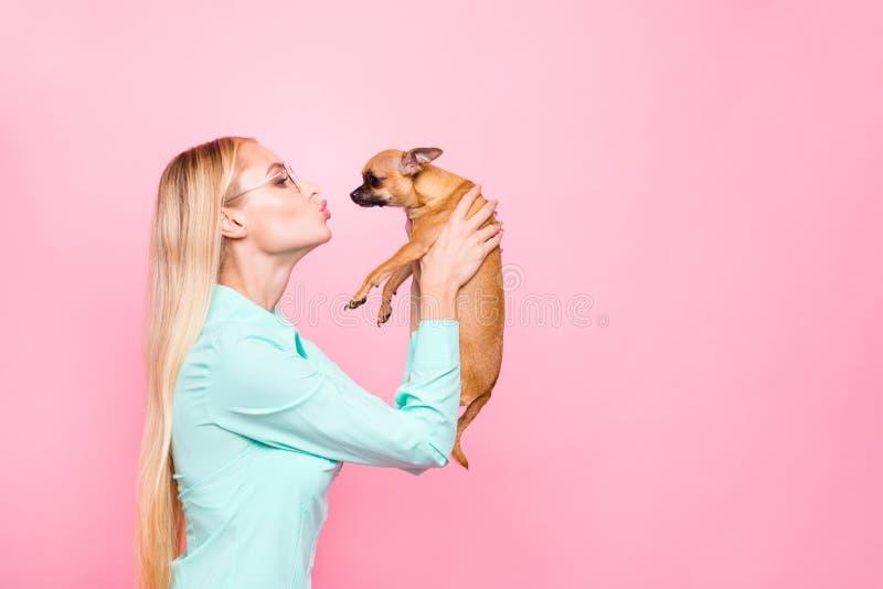 Profilsidofoto av att charma ungdom med eyewearglasögon som rymmer hennes husdjur som kysser det utbildande bärande turkosskjorta arkivfoto