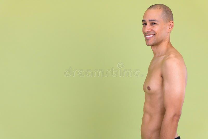 Profilsikt av den lyckliga skalliga mång- etniska mannen som ser den shirtless kameran fotografering för bildbyråer
