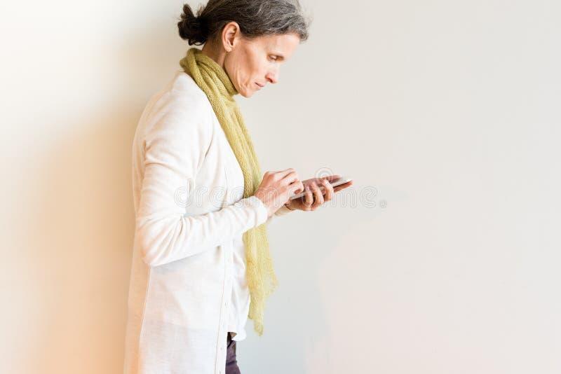 Profilsikt av den mogna kvinnan som använder den smarta telefonen fotografering för bildbyråer