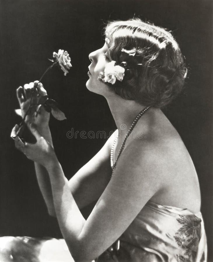Profilsikt av den unga kvinnan som luktar blomman arkivbild