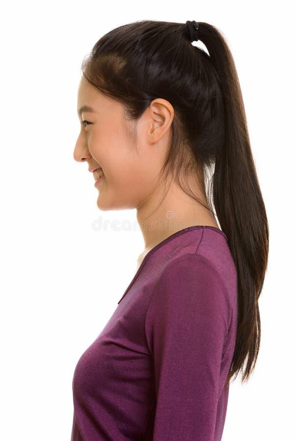 Profilsikt av ungt lyckligt asiatiskt le för tonårs- flicka arkivfoto