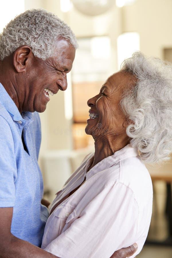 Profilskott som ?lskar h?ga par som hemma kramar tillsammans royaltyfria bilder