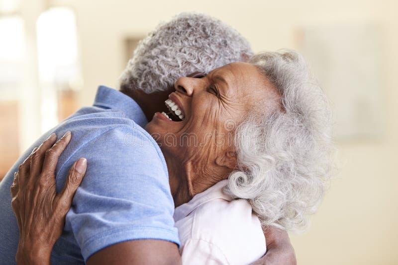 Profilskott som ?lskar h?ga par som hemma kramar tillsammans arkivfoto