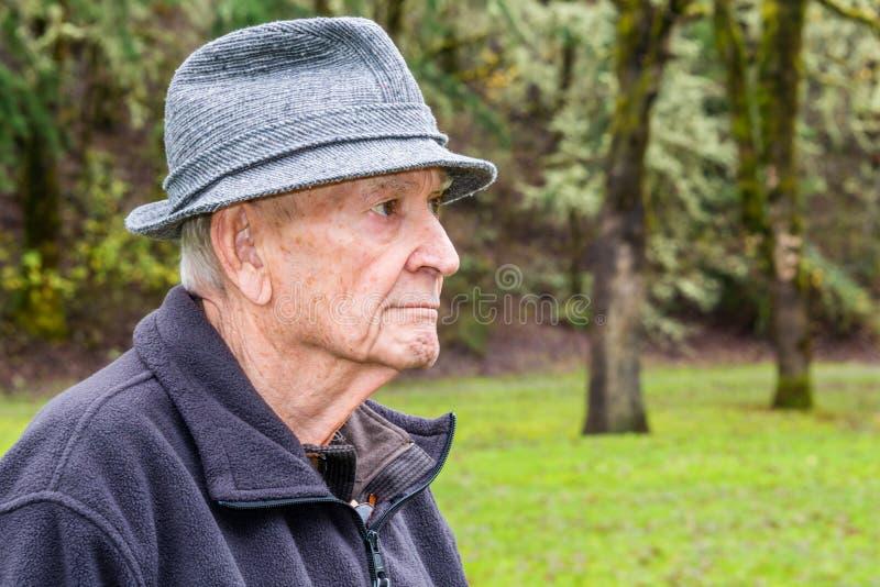 Profilstående av den allvarliga äldre mannen med Grey Tweed Rain Hat a royaltyfria foton