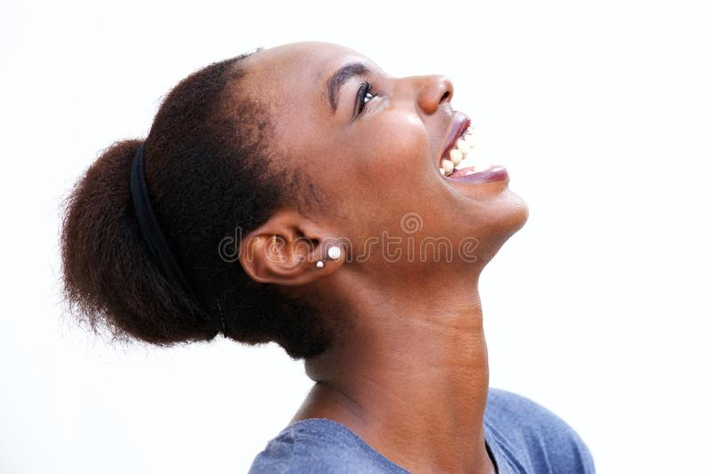 Profilstående av den härliga unga afrikansk amerikankvinnan som skrattar och ser upp arkivbild