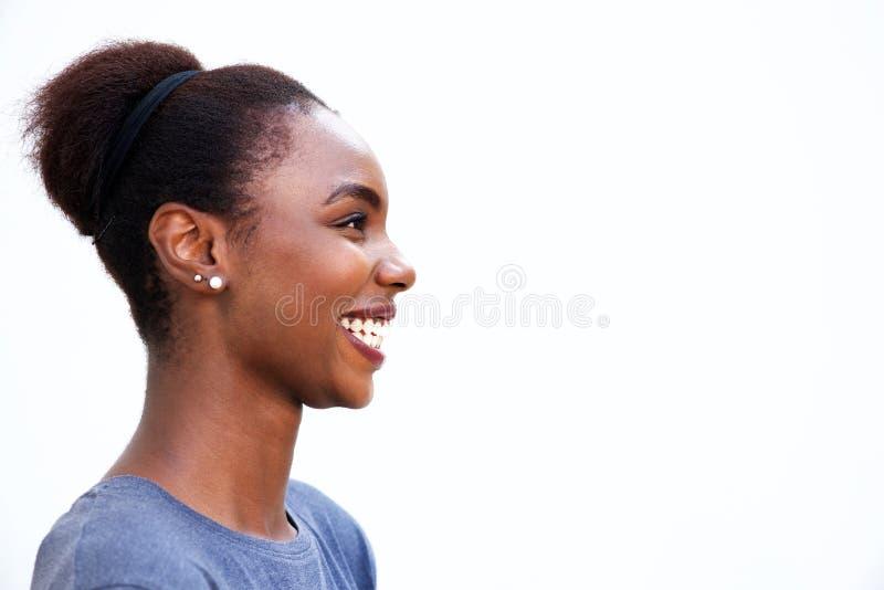 Profilstående av den lyckliga unga afrikanska kvinnan som skrattar mot isolerad vit bakgrund royaltyfri bild
