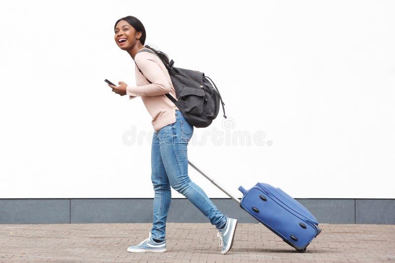 Profilstående av den unga kvinnliga handelsresanden som går med mobiltelefonen och resväskan mot den vita väggen royaltyfri fotografi