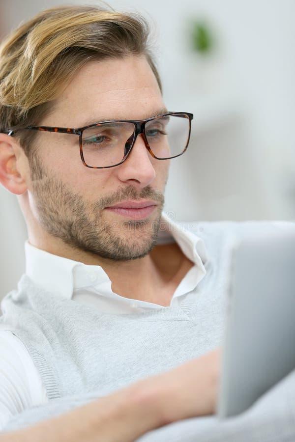 Profilstående av den unga mannen som använder minnestavlan royaltyfria bilder