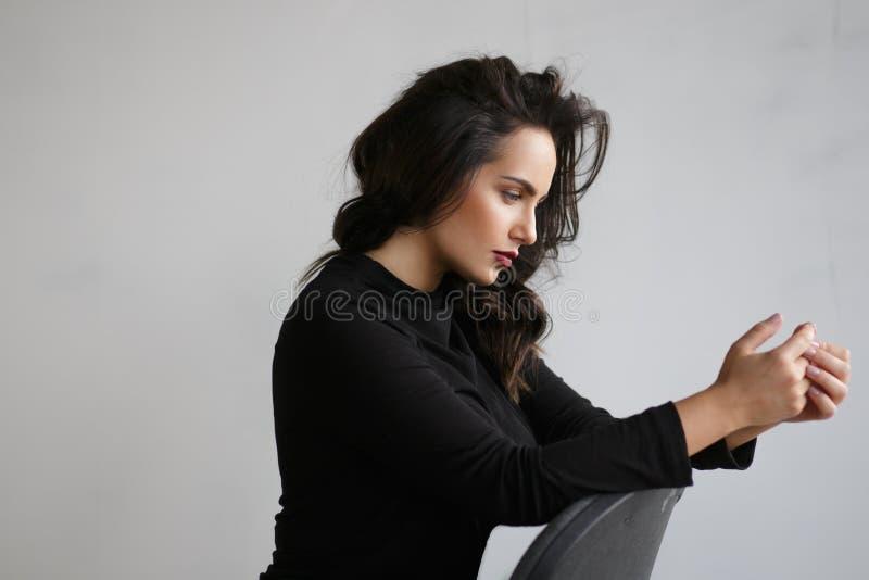 Profilstående av en härlig eftertänksam kvinna i svart som placeras på stol i studio, på en grå bakgrund arkivbilder