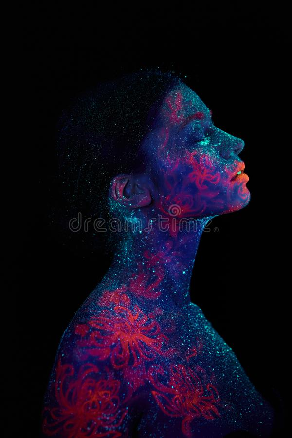 Profilstående av en härlig flickafrämling Ultraviolett himmel för natt för blått för kroppkonst med stjärnor och den rosa manet royaltyfri bild