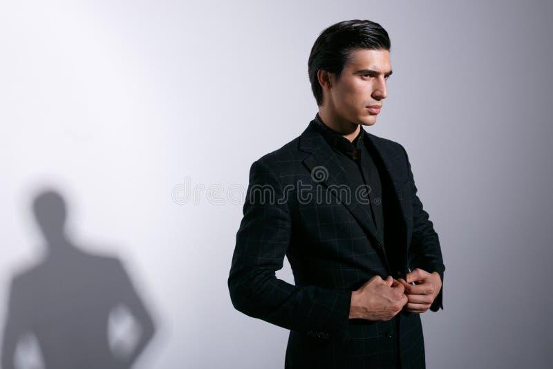Profilståenden av den stilfulla mannen i elegant dräkt, poserar och se en sida bort Horisontalsikt, med kopieringsutrymme arkivfoto