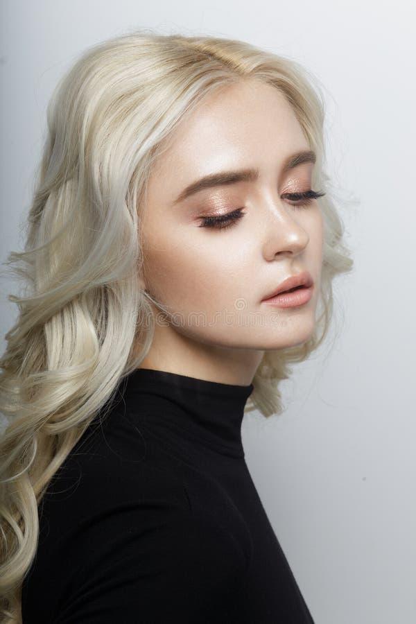 Profilståenden av en kvinna med den lockiga blonda frisyren som är mjuk utgör, med stängda ögon som isoleras på en vit bakgrund royaltyfri fotografi